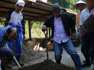 用土を険しい顔で眺める男たち。スコップを持って土づくりに励んでいます。