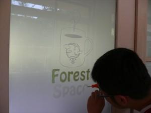 ルーターでドアのガラスを削りロゴマークをほっています